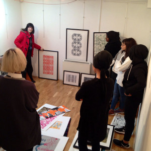Students work collectively to decide how to hang their work.